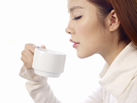 side view of young woman drinking coffee with eyes closed  photo