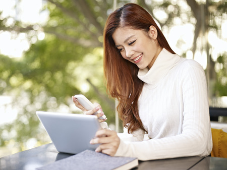 mobile shop: asian young woman working with mobile phone and tablet computer in coffee shop