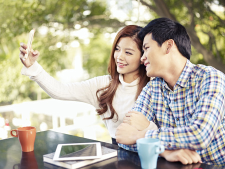 happy asian couple: young couple taking selfie in coffee shop