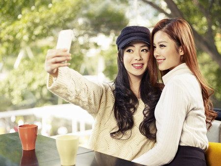 korean woman: young friends taking selfie in coffee shop  Stock Photo