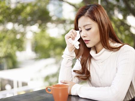 fille qui pleure: jeunes larmes femme d'essuyage avec un tissu facial