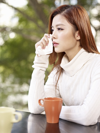 young woman wiping tears with facial tissue
