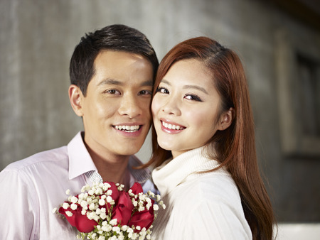 happy young couple smiling with flowers
