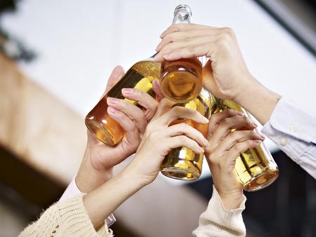 beer bottles raised for a toast  Banco de Imagens