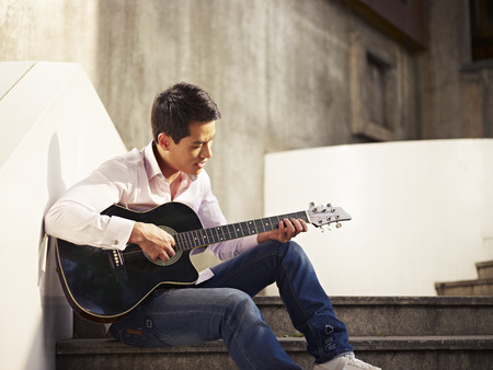 street musician: young man sitting on steps playing guitar and singing