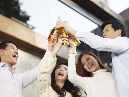 tomando alcohol: j�venes amigos que cr�an botella de cerveza para un brindis Foto de archivo