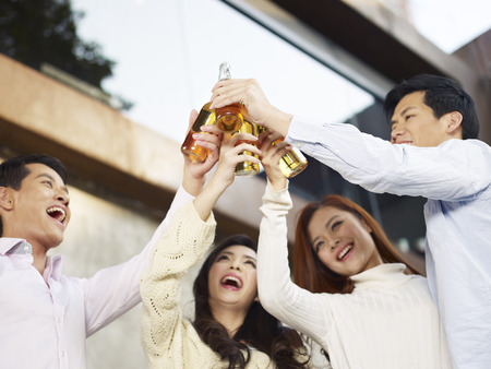 east asian culture: young friends raising beer bottle for a toast  Stock Photo