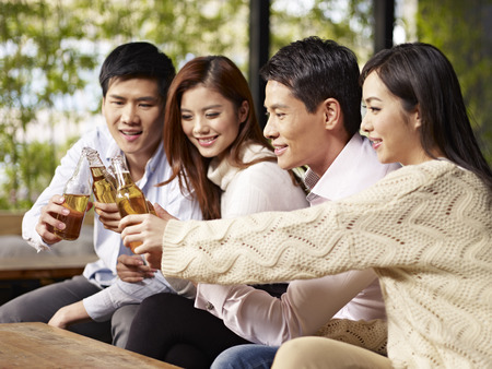 social drinking: young asian friends gathering chatting drinking beer  Stock Photo