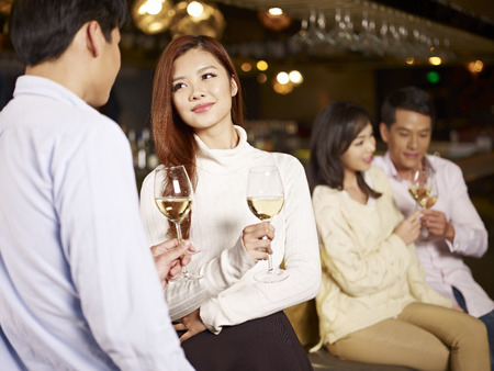 gathering: young asian friends couples enjoying party in pub
