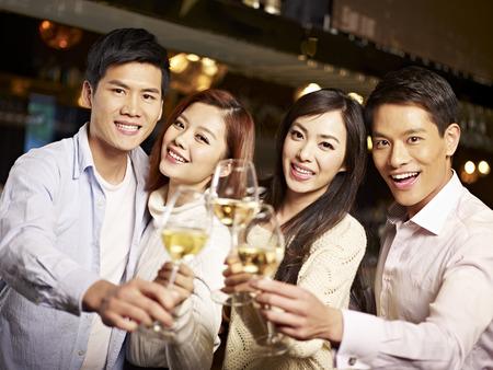 personas festejando: amigos asiáticos jóvenes parejas que disfrutan de fiesta en el pub Foto de archivo