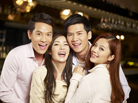 young people fun: young asian friends couples enjoying party in pub