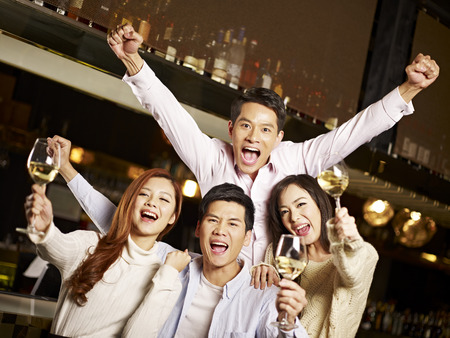 people partying: young asian friends couples enjoying party in pub