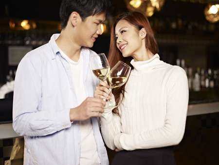 good mood: young asian couple enjoying wine in pub