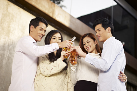 clinking: young asian adults toasting with beer  Stock Photo