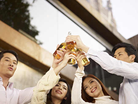 young asian adults toasting with beer  photo