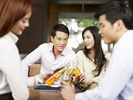 two young asian couples drinking beer together