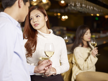 young asian couple having a conversation in bar  photo