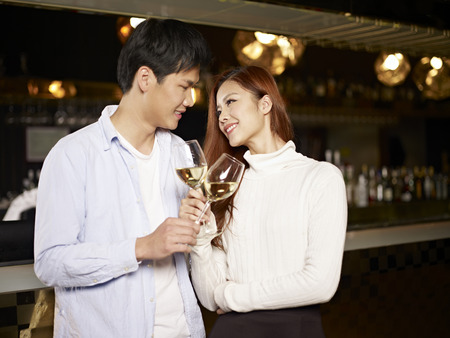young asian couple enjoying a conversation in bar  photo