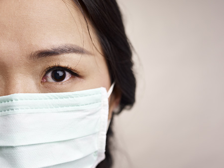 smog: face of a mask-wearing woman with fear in the eye