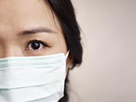 gezicht van een masker dragen van vrouw met angst in de ogen Stockfoto