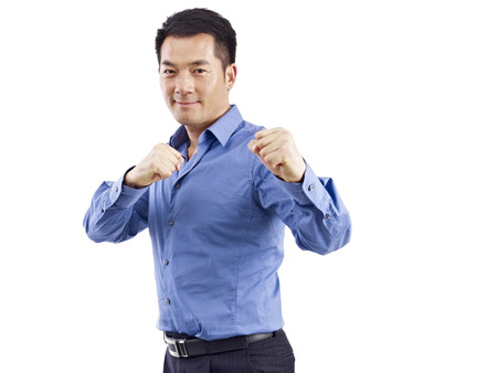 competitiveness: asian businessman in martial art posture, isolated on white