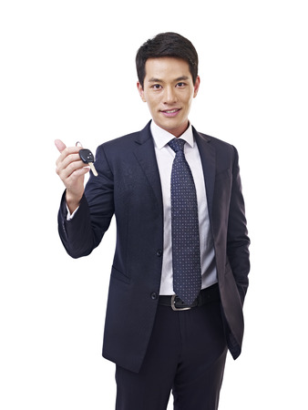 salesmen: young asian car salesman holding car key, isolated on white
