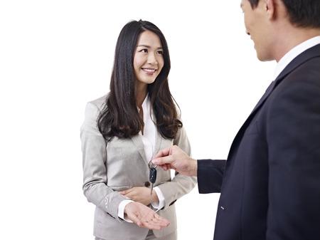 young car salesman handing car key to young woman