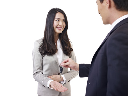 young car salesman handing car key to young woman  photo