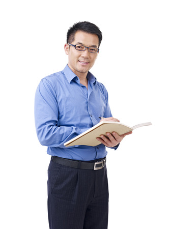 maestra ense�ando: Hombre asi�tico con la pluma y el cuaderno, aislado en blanco Foto de archivo