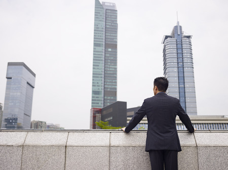 pressured: rear view of an asian businessman