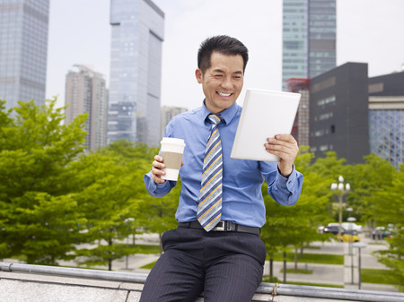 asian businessman looking at tablet holding coffee cup smiling