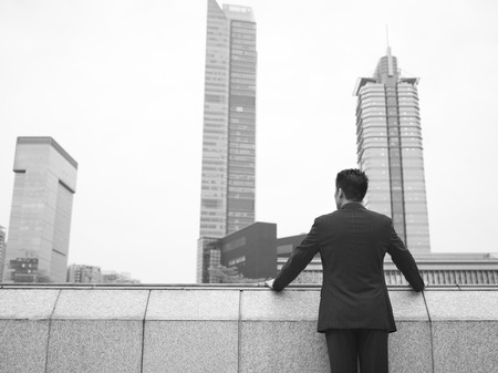 indecisiveness: rear view of an asian businessman, black and white  Stock Photo