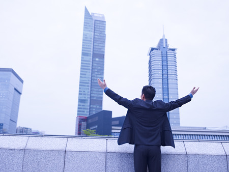 asian businessman looking at city with open arms  photo