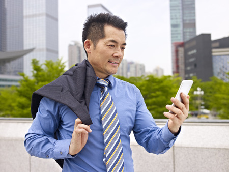 asian businessman looking at cellphone