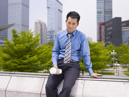 bad mood: frustrated asian business executive sitting in city park  Stock Photo