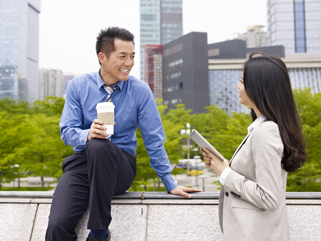 asian businessman and businesswoman talking outdoors  photo