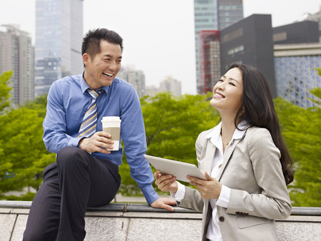 east espresso: asian businessman and businesswoman talking outdoors