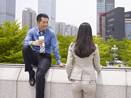 hair back: asian businessman and businesswoman talking outdoors
