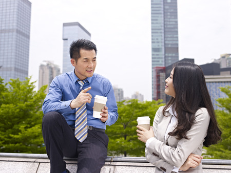 taking a break: asian businessman and businesswoman talking outdoors