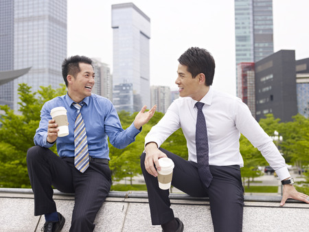 teammates: two asian business executives talking in city park while taking a coffee break. Stock Photo