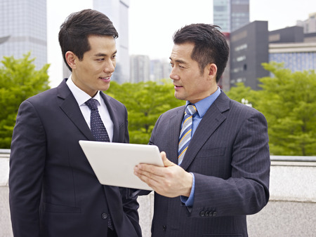 relaxed business man: asian businessmen discussing business outdoor. Stock Photo