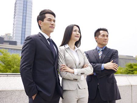 challenges ahead: outdoor portrait of an asian business team.