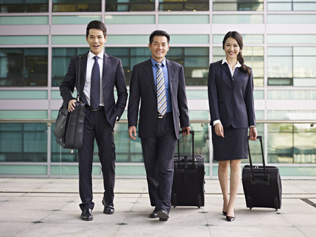 vigorously: business people traveling with luggages.