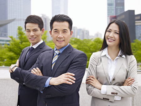 young man smiling: outdoor portrait of an asian business team.