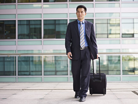 korean man: businessperson traveling with luggage.