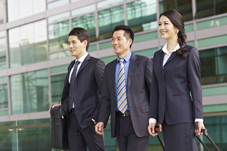 dragging: team of asian business people with modern building background. Stock Photo