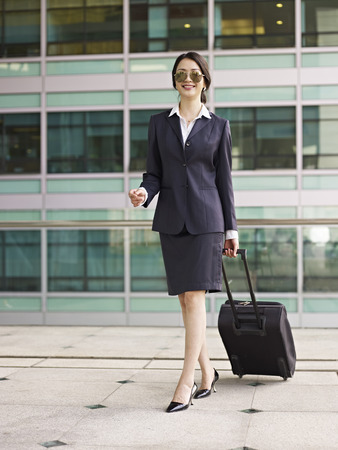 dragging: female asian business traveler with suitcase.