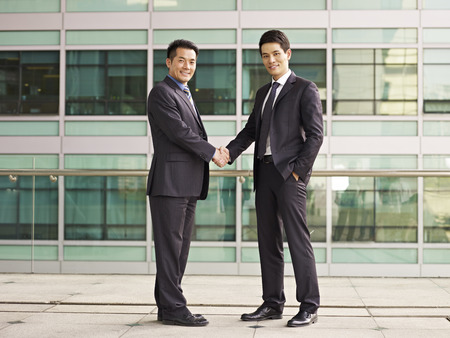 asian businessmen shaking hands looking at camera smiling. Imagens