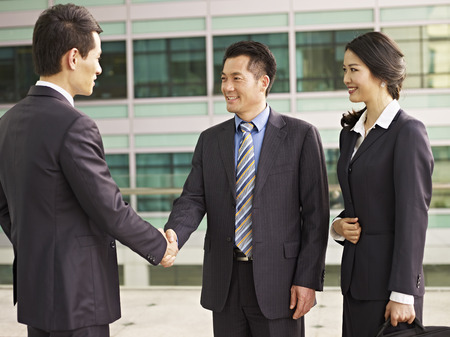 asian businesspeople shaking hands and smiling.