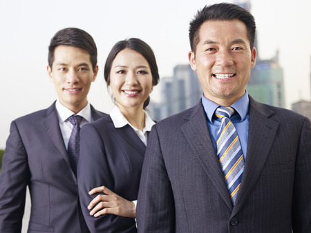 hong: portrait of an asian business team, focus on the man in front.